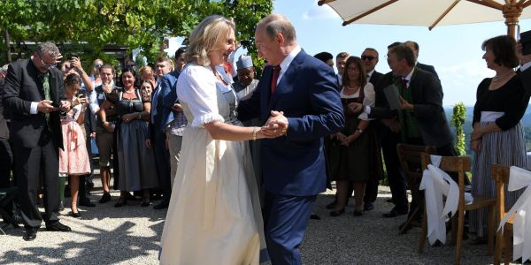 Russian President Vladimir Putin gives Austria's foreign minister an intense stare as he dances with her on her wedding day
