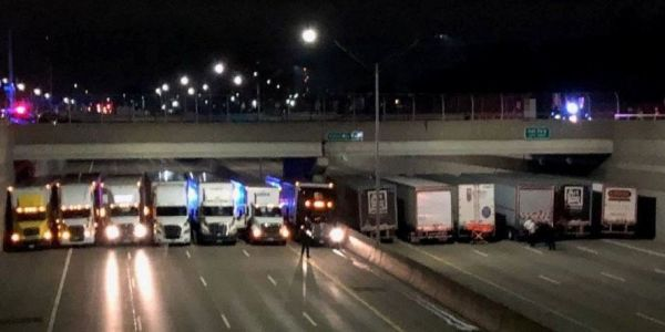13 trucks line up under a bridge to stop a man from contemplating suicide on Michigan freeway